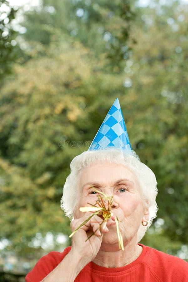 Старшая женщина на вечеринке по случаю дня рождения стоковое изображение