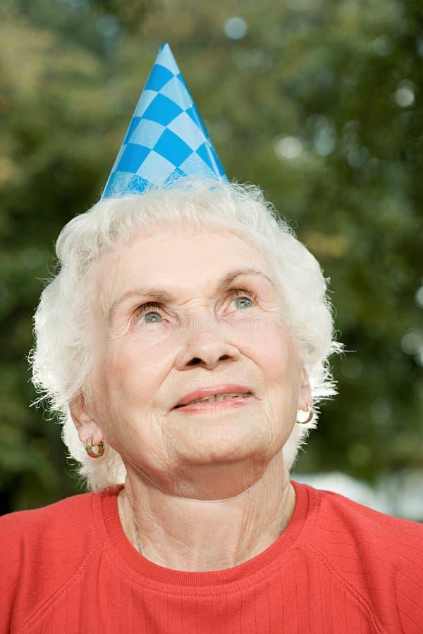 Старшая женщина на вечеринке по случаю дня рождения стоковая фотография