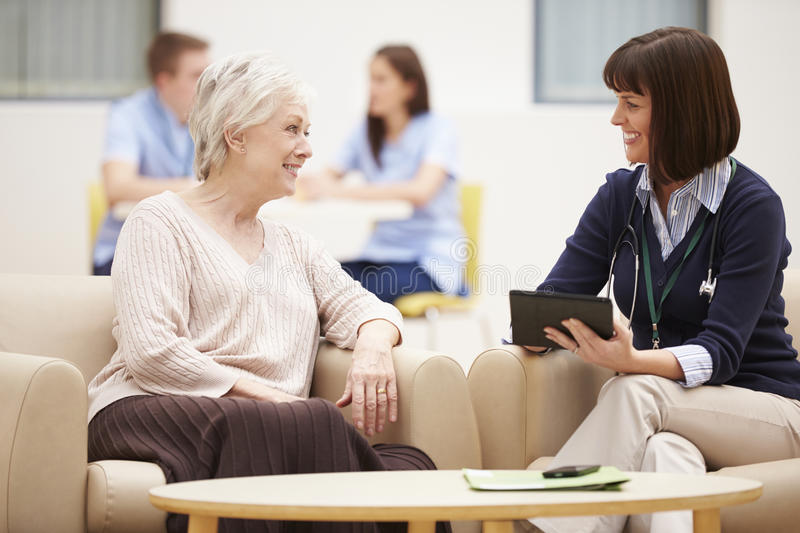 Старшая женщина обсуждая результаты теста с доктором стоковые фото