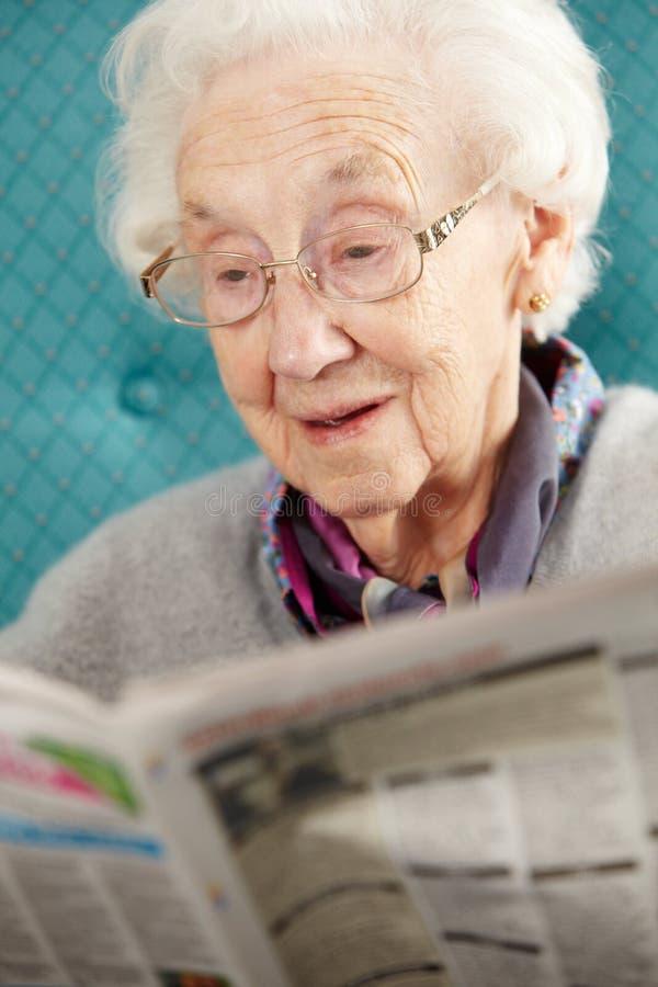Старшая женщина ослабляя в газете чтения стула стоковое фото
