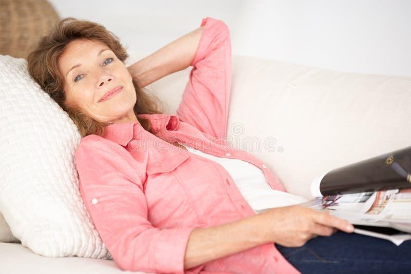 Старшая женщина ослабляя дома стоковое фото rf