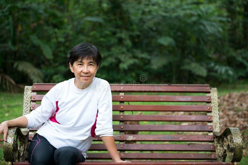 Старшая женщина ослабляя на скамейке в парке стоковая фотография