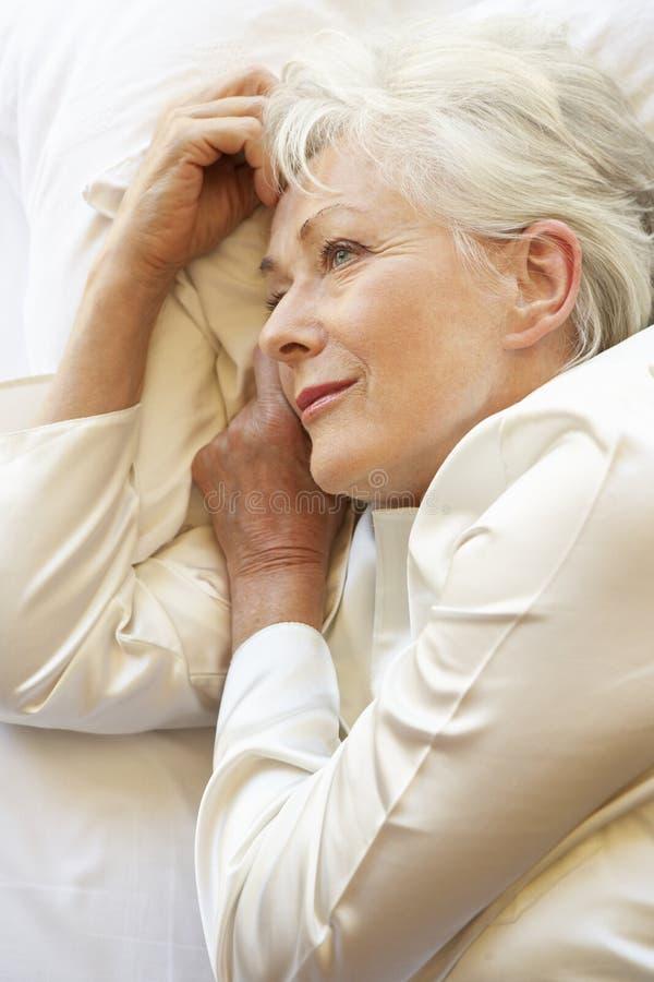Старшая женщина ослабляя в кровати стоковое фото rf
