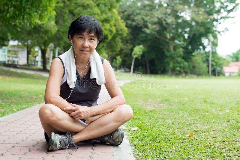 Старшая женщина отдыхая после jogging стоковое изображение
