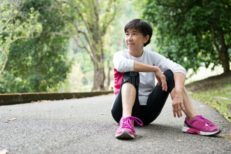 Старшая женщина отдыхая после jogging стоковые изображения rf