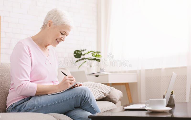 Старшая женщина перезаписывая рецепт от ноутбука к тетради стоковые фото