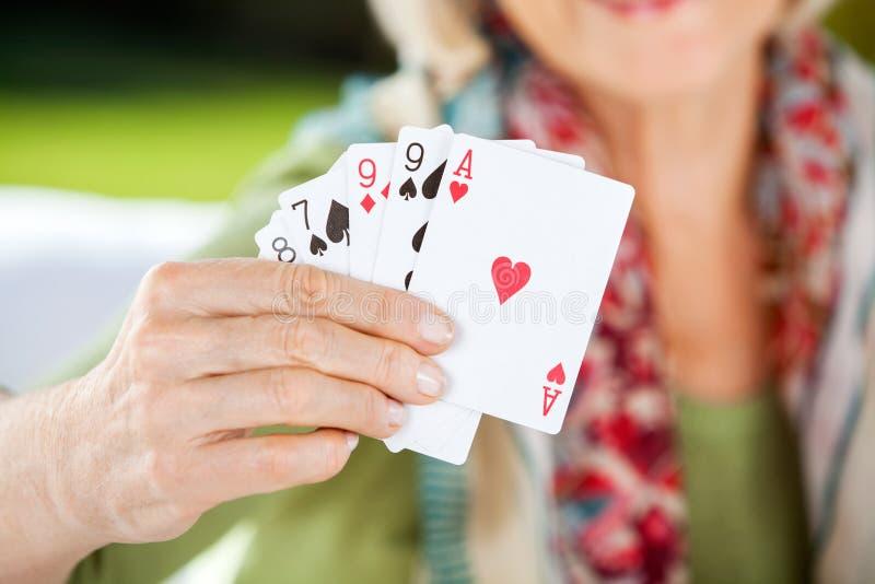 Старшая женщина показывая играя карточки стоковые фотографии rf