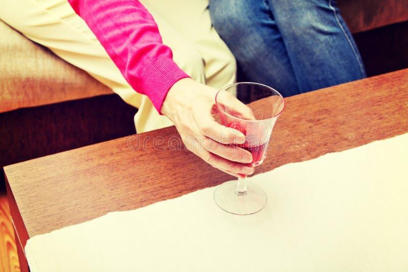 Старшая женщина положила бокал вина на таблицу стоковые фото
