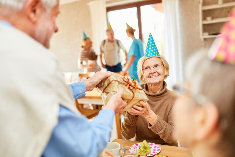 Старшая женщина получает подарок на день рождения стоковая фотография rf