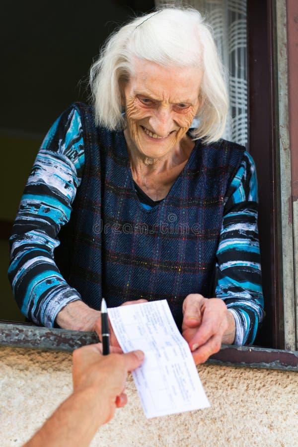 Старшая женщина получая проверку выхода на пенсию дома стоковая фотография rf