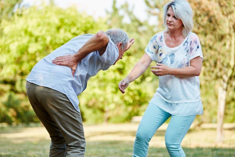 Старшая женщина помогает человеку имея боль люмбаго стоковая фотография rf