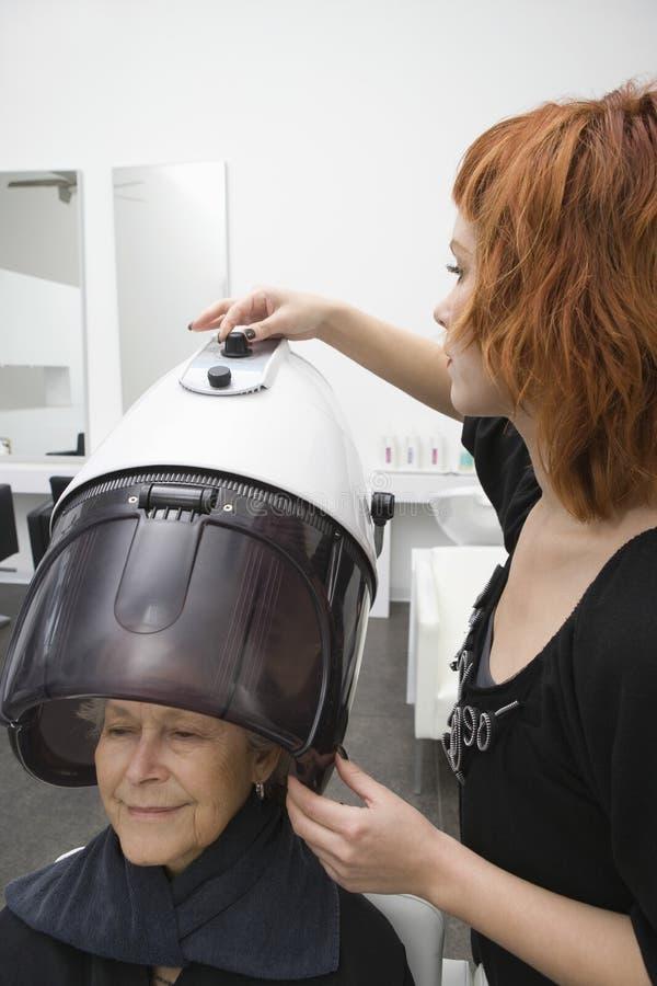 Старшая женщина под с капюшоном феном для волос в салоне стоковое фото rf