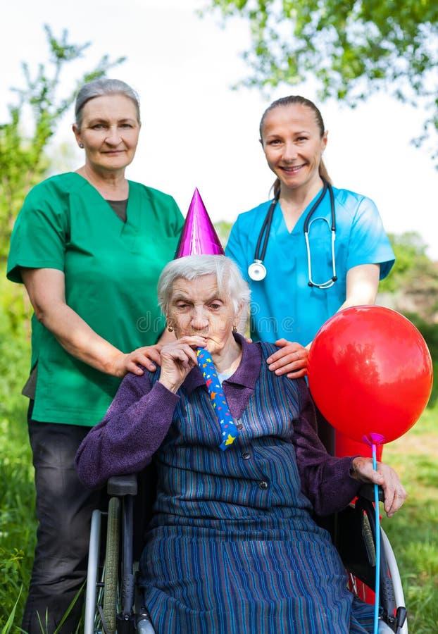 Старшая женщина празднуя день рождения стоковые изображения