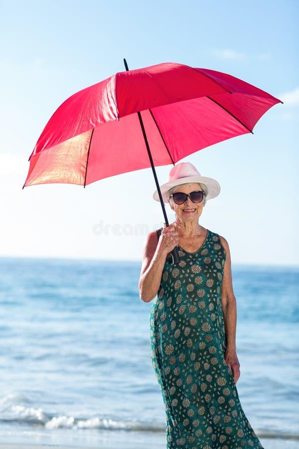 Старшая женщина представляя с зонтиком стоковая фотография rf