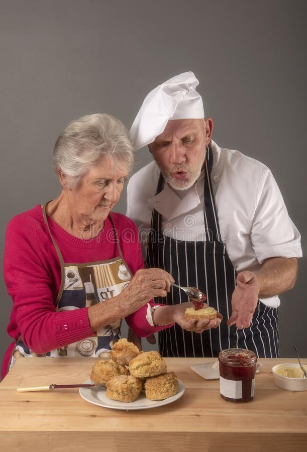 Старшая женщина принимая варящ уроки со зрелым шеф-поваром стоковое фото rf