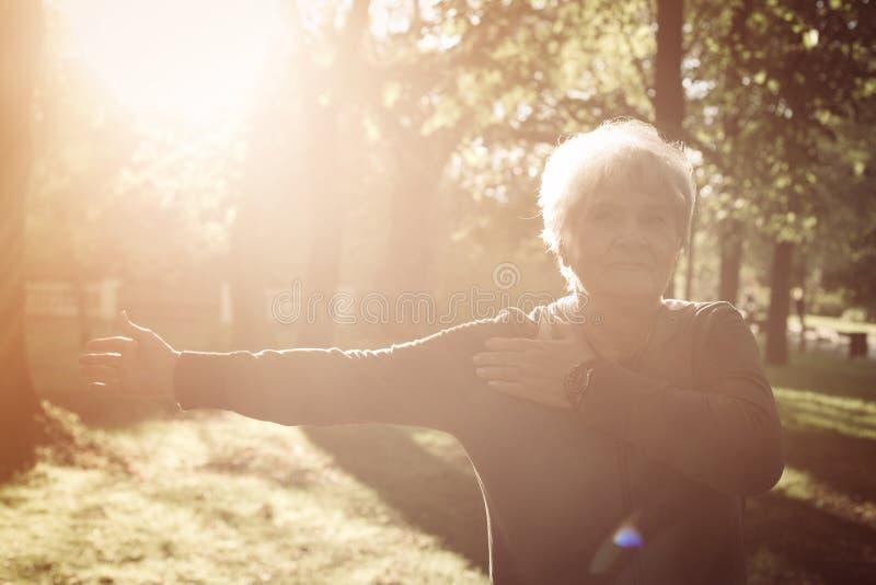 Старшая женщина протягивая руку и работая в alon парка стоковое фото