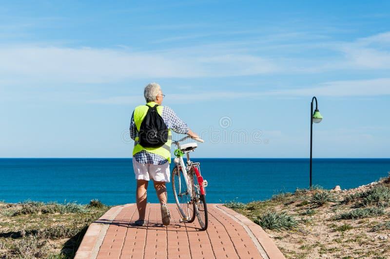 Старшая женщина путешествуя с велосипедом стоковая фотография