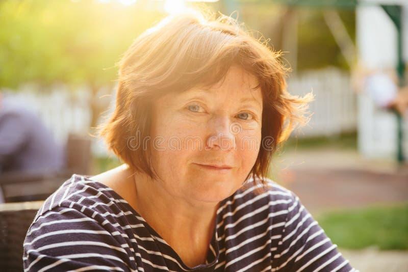 Старшая женщина расслабленная и счастливая на заходе солнца стоковое фото rf