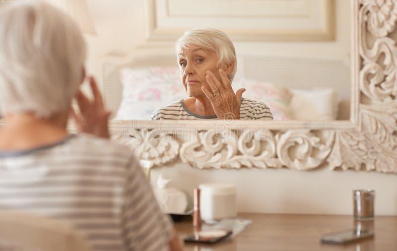 Старшая женщина рассматривая ее сторону в зеркале стоковые фотографии rf