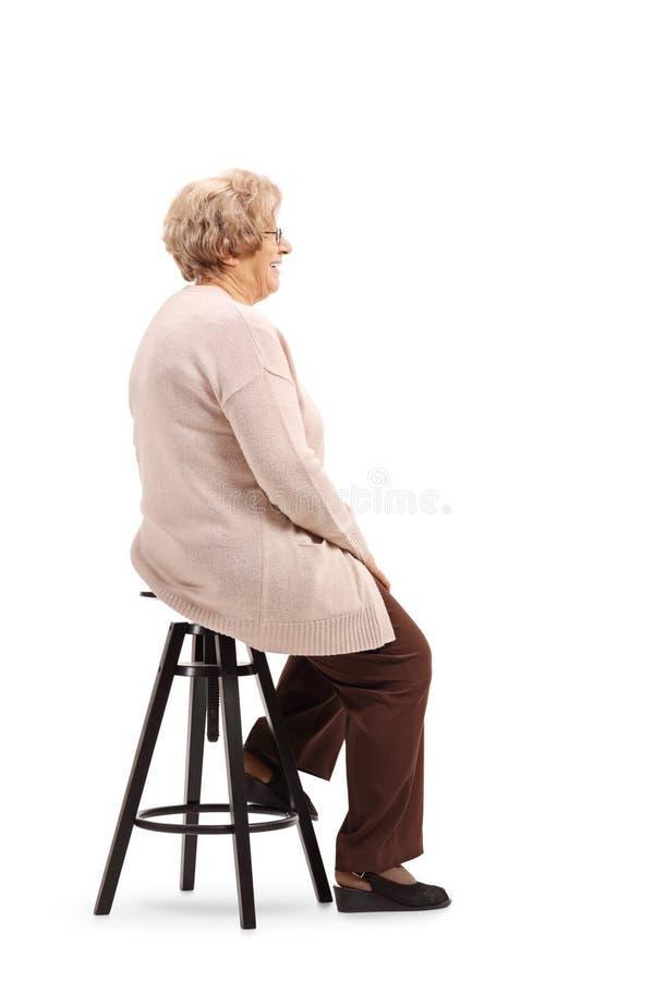 Старшая женщина сидя на стуле и представлять табуретки стоковая фотография