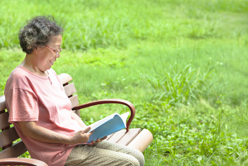 Старшая женщина сидя на стенде и читая книгу стоковое фото