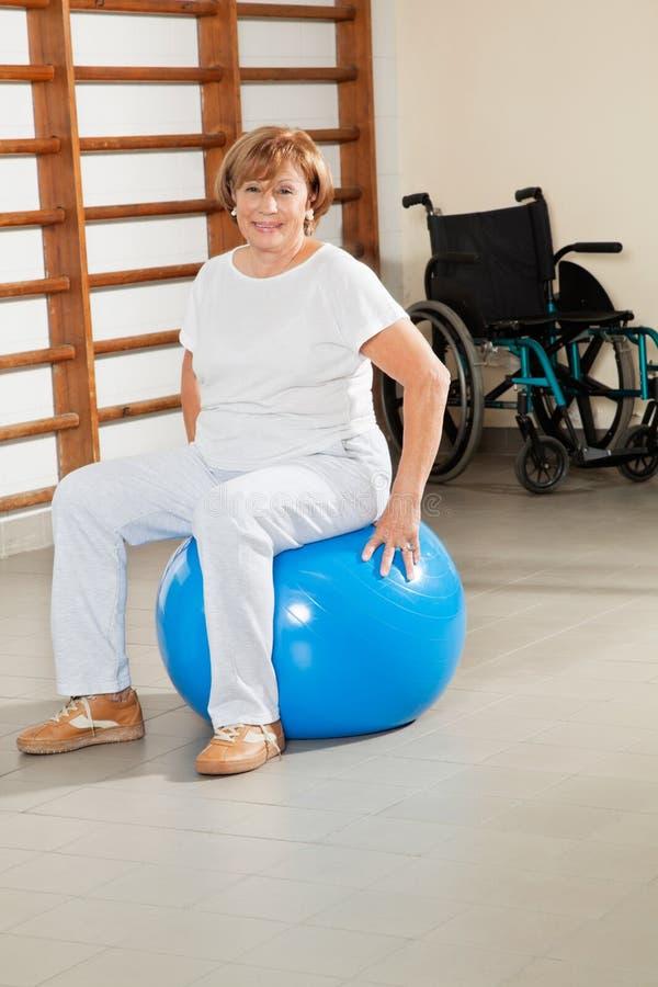 Старшая женщина сидя на шарике фитнеса стоковые изображения