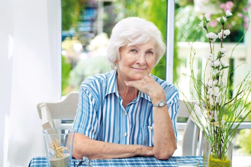 Старшая женщина сидя дома стоковое фото