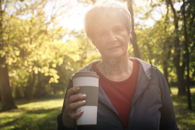 Старшая женщина стоя в парке смотря камеру и владение стоковое изображение
