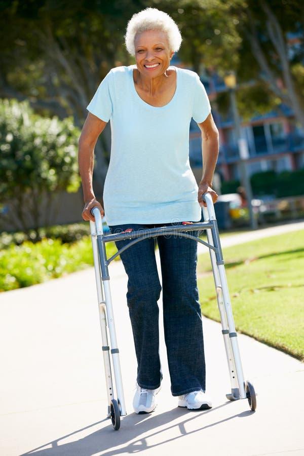 Старшая женщина с гуляя рамкой стоковое фото rf
