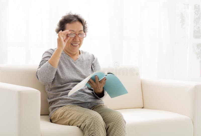 Старшая женщина с книгой в живущей комнате стоковое изображение rf