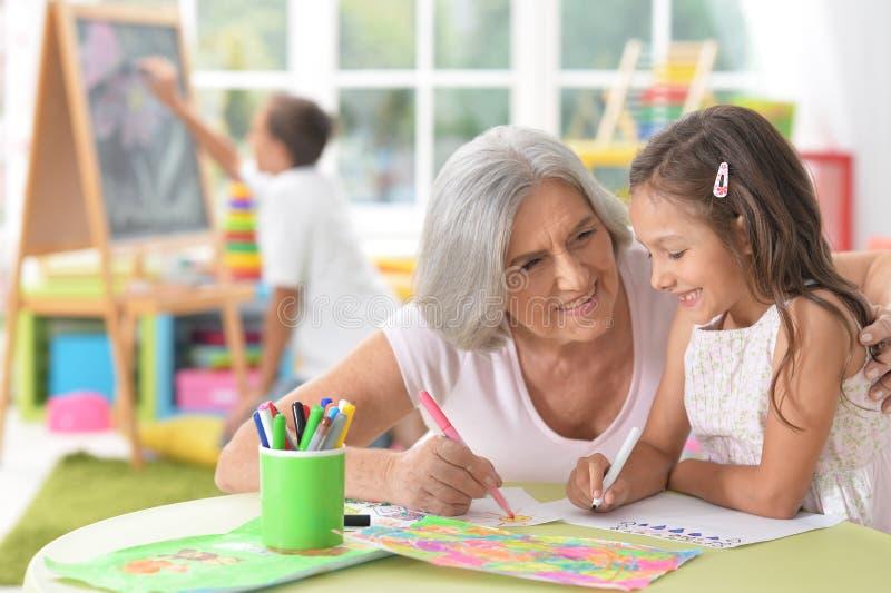 Старшая женщина с маленькой школьницей на классе стоковая фотография