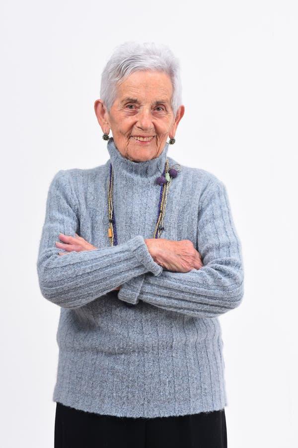 Старшая женщина с оружиями пересеченными на белую предпосылку стоковые изображения
