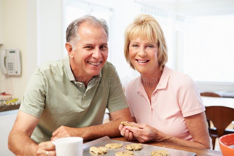 Старшая женщина с печеньями выпечки супруга в кухне стоковое изображение