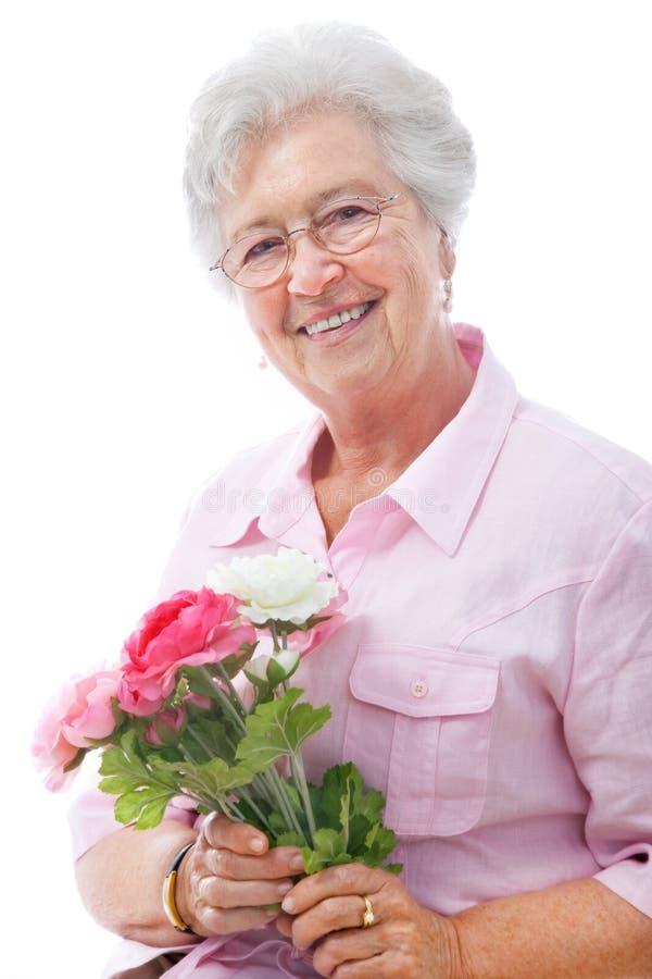 Старшая женщина с пуком цветков стоковое фото