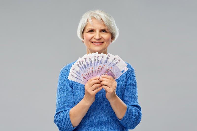 Старшая женщина с сотнями банкнот денег евро стоковая фотография rf