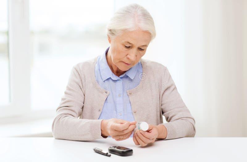 Старшая женщина с glucometer проверяя уровень сахара в крови стоковая фотография rf