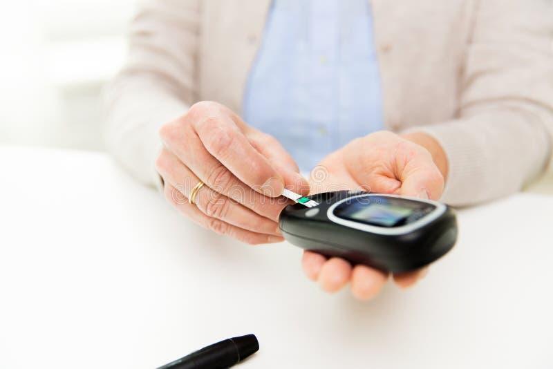 Старшая женщина с glucometer проверяя уровень сахара в крови стоковое фото