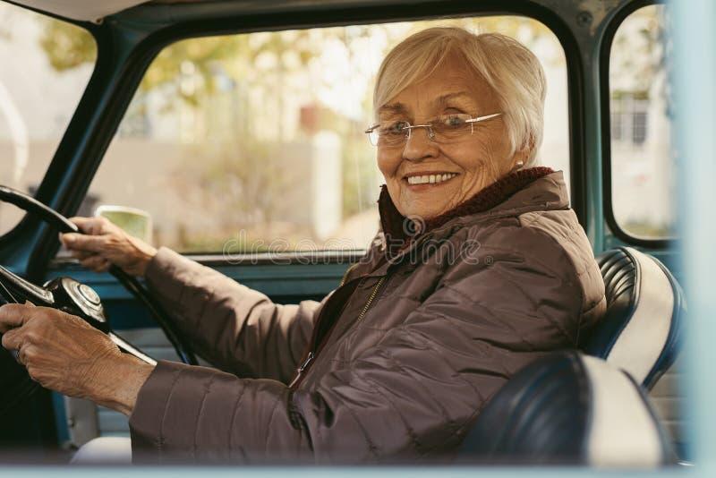 Старшая женщина управляя автомобилем на зимний день стоковые изображения rf