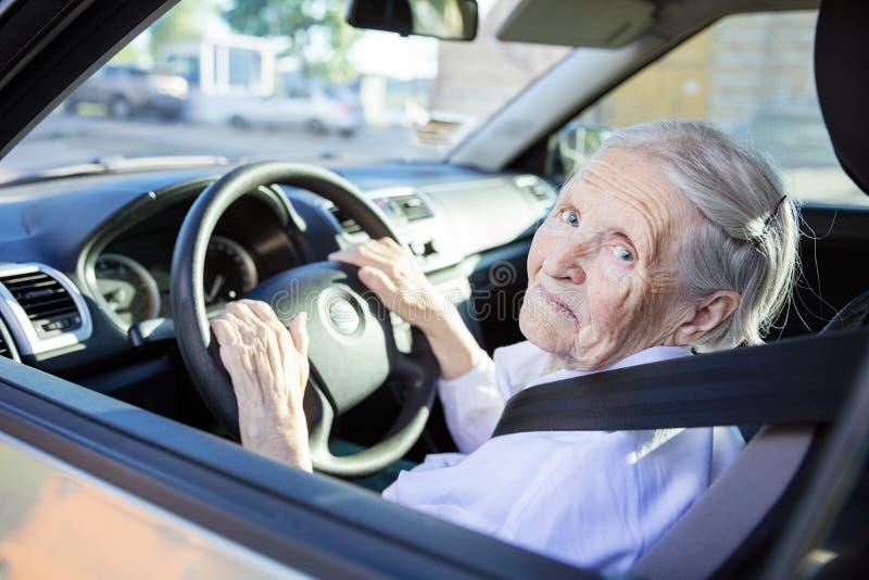Старшая женщина управляя автомобилем на солнечный день стоковое фото rf