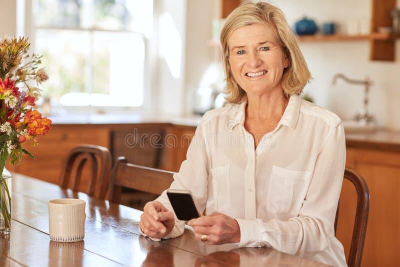 Старшая женщина усмехаясь пока держащ телефон в ее кухне стоковые фотографии rf