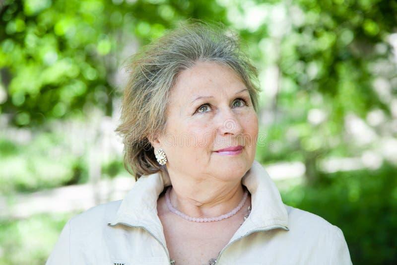 Старшая женщина outdoors в парке смотря вверх стоковая фотография rf