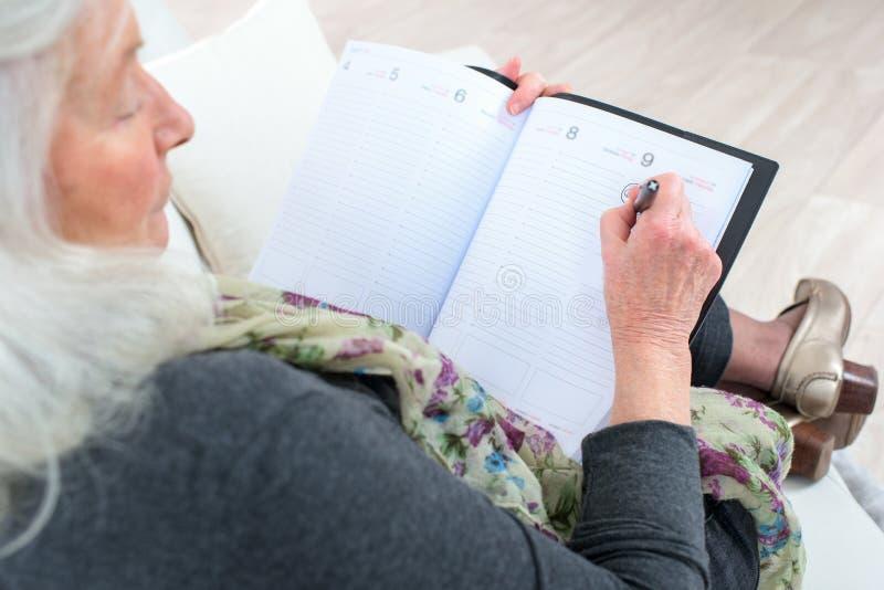 Старшая исполнительная власть женщины с план-графиком и сотовым телефоном стоковые фото