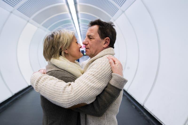 Старшая пара в зиме одевает в прихожей обнимать метро стоковая фотография