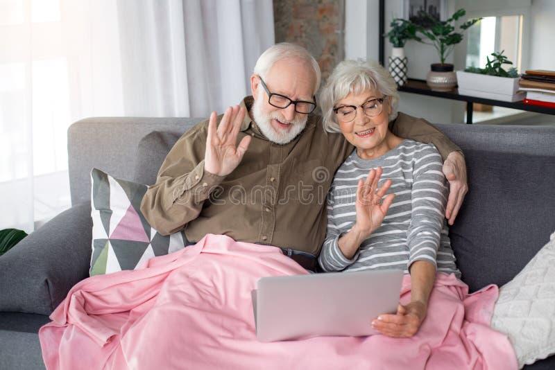 Старшая пара связывает с семьей через интернет стоковые фото