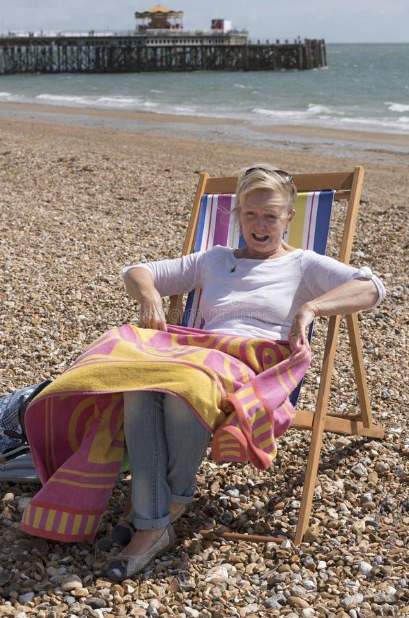 Старшая персона сидя в deckchair на пляже стоковая фотография rf