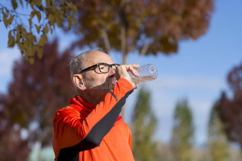 Старшая питьевая вода бегуна после jogging стоковые изображения
