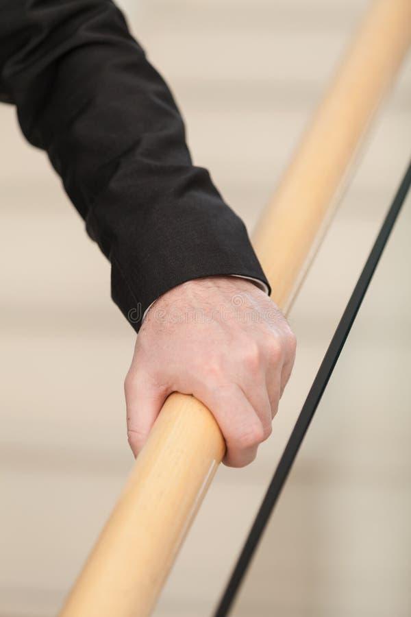 Старшая рука схватывает деревянные перила стоковые фотографии rf