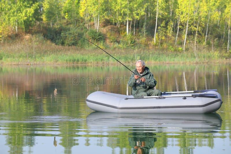 Старшая рыбная ловля от его шлюпки на солнечный день осени стоковые изображения rf