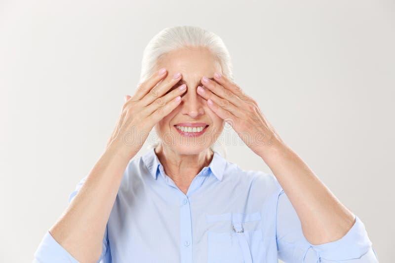 Старшая седая женщина покрывая ее глаза с обеими руками стоковые изображения