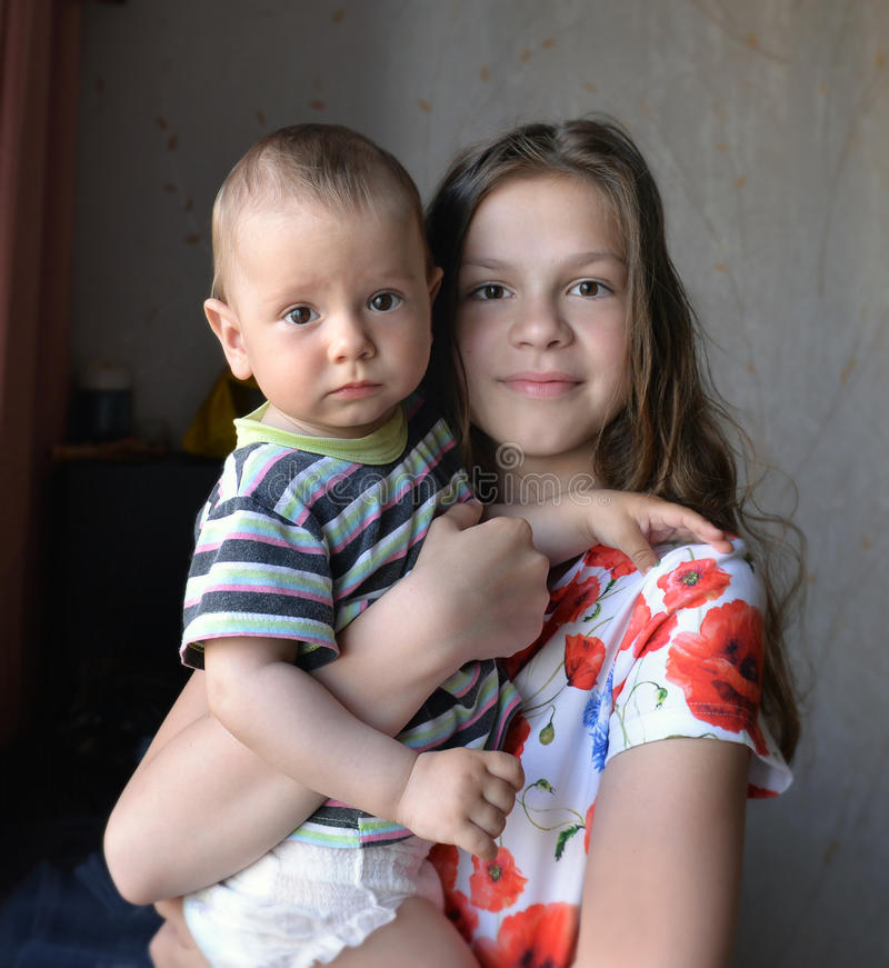 Старшая сестра держит малого брата в ее оружиях стоковое изображение rf